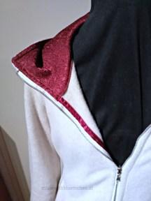 Rotes Brokat-Kaputzenfutter und rotes Webband zur inneren Versäuberung des Reißverschlusses