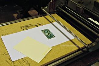 Auf der Presse wird das Liolstück ausgerichtet, dann die vorbereitete Karte drauf.