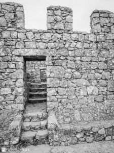 three steps leading to a doorway set in a stone wall leading to a further set of steps