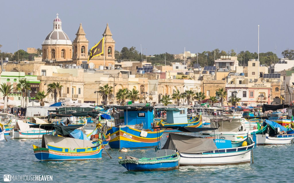 Colourful blue fishing boats in Marsaxlokk harbour with white stone city in background - Malta Megalithic to Modern