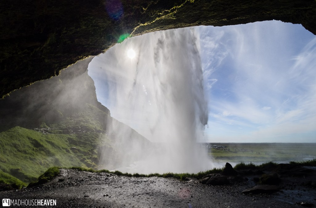 Standing right behind the Seljalandsfoss waterfall, looking at the vast Icelandic expanse behind