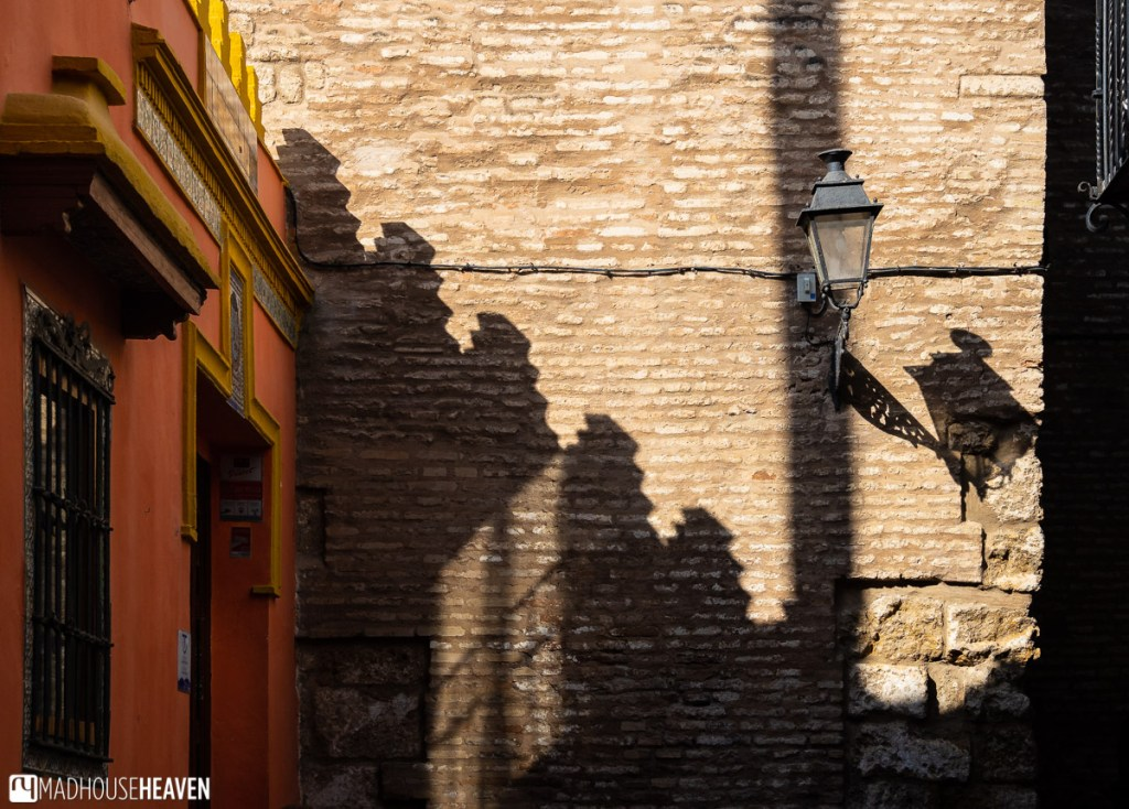 Graphic shadows cast across a brick wall reveal the Islamic influence in the building behind