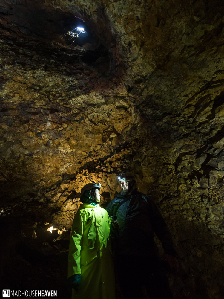 Two people shining light at each other at the bottom of the Thrihnukagigur Volcano, the elevator seen high above them