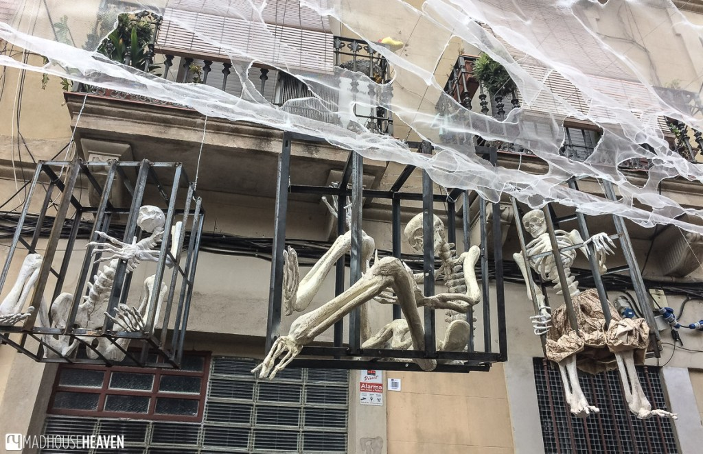 Skeletons hanging in cages over a street in Barcelona
