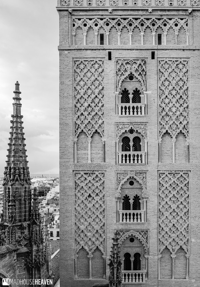 Black and white image of the Gothic spire of the Seville Cathedral next to the Islamic architecture of the Giralda Tower