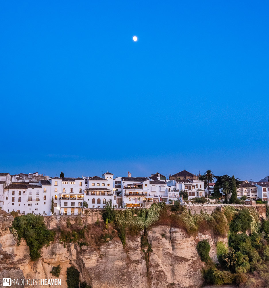The last rays of the setting Sun give the white facades of the Ronda old town a warm glow