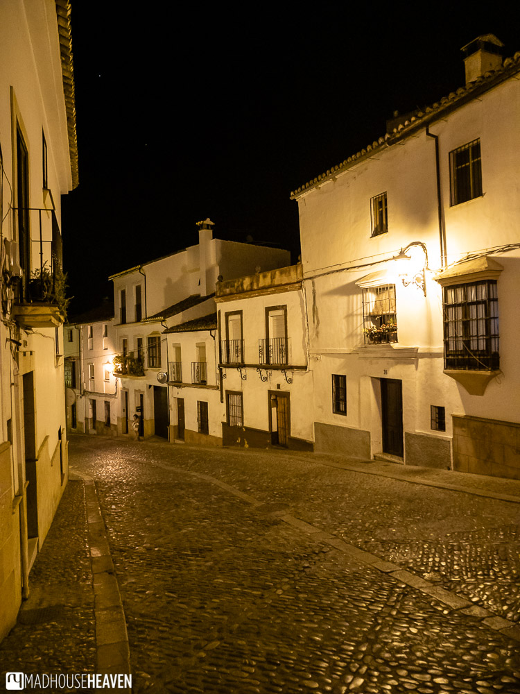 Empty cobblestoned street of Ronda at night, the street lights giving it an eerie yellow glow