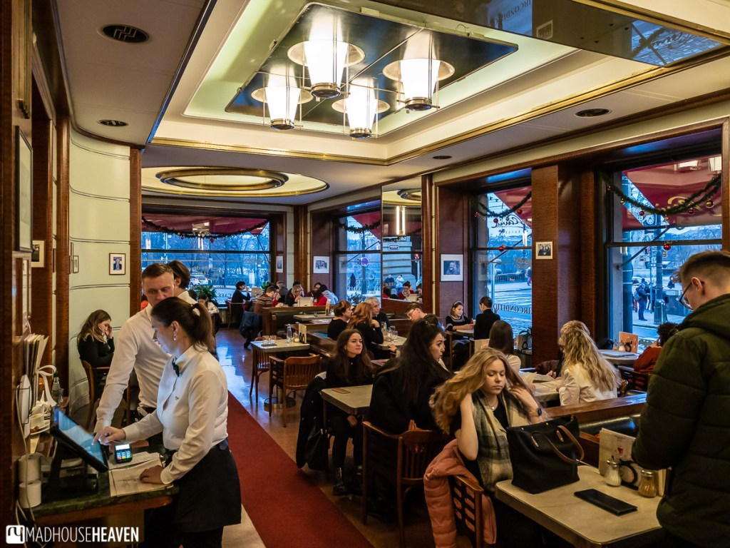 The warm interior of a Prague grand café, filled with patrons and waiters