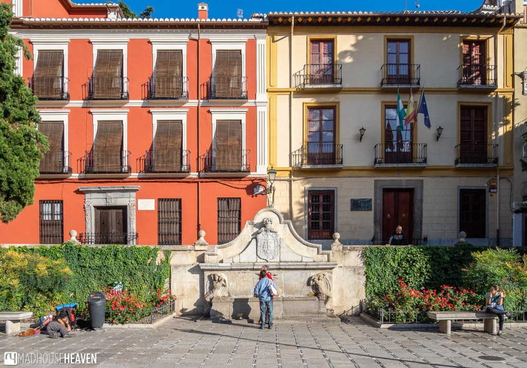 A Spanish courtyard with a fountain, surrounded by colourful buildings, bathed in golden sunlight