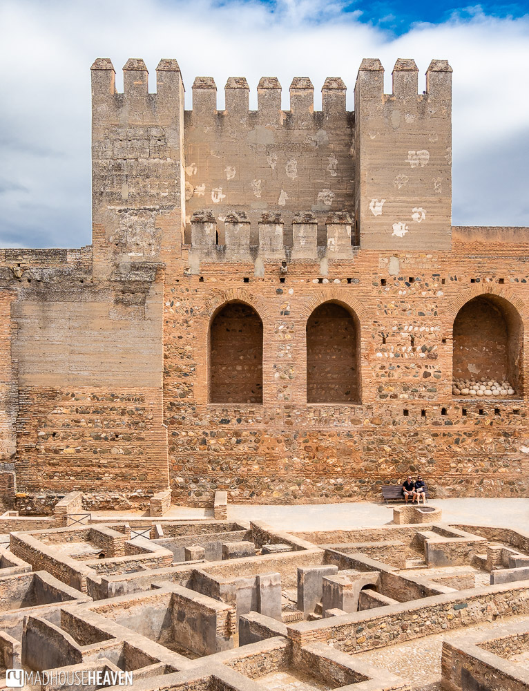 The tower at the entrance to the Alcazaba, with its massive ramparts, and a couple of tourists sitting under the weathered walls