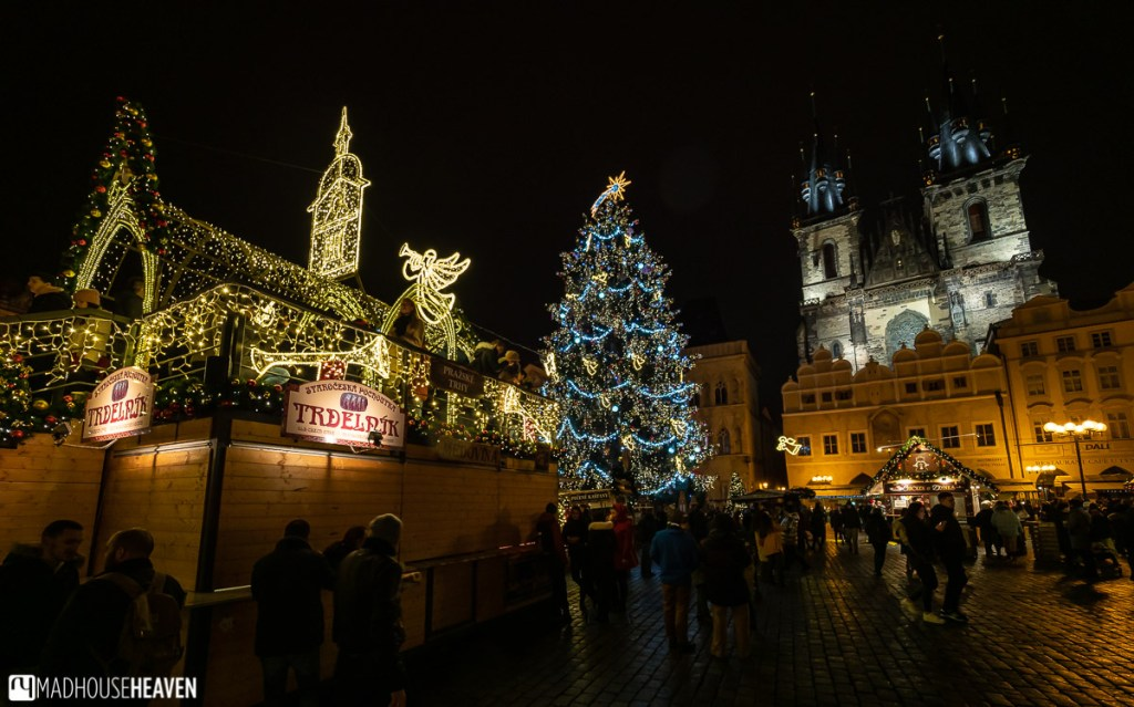 Prague's Christmas market lit by warm yellow lights late at night