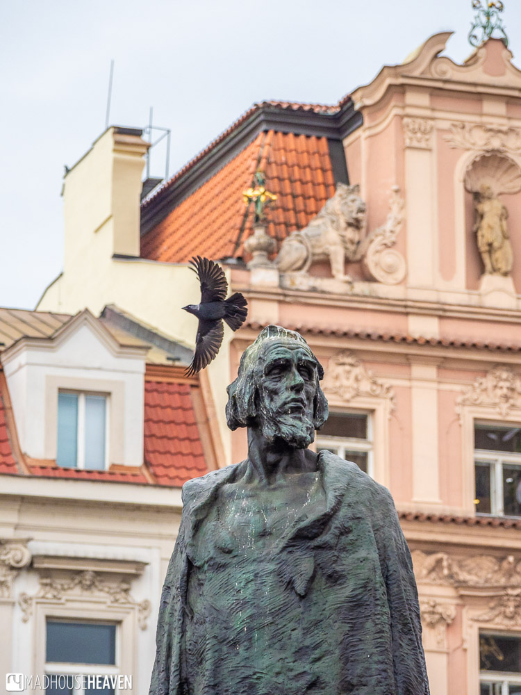 A close up of the Jan Hus monument, showing the face of Jan Hus, and a black bird flying around him