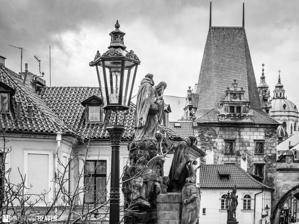 A view from Charles Bridge, with an old style lamp, a statue and Gothic roofs in the background