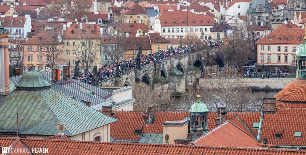 A view from above of Charles' bridge, packed with tourist, surrounded by secessionist style buildings