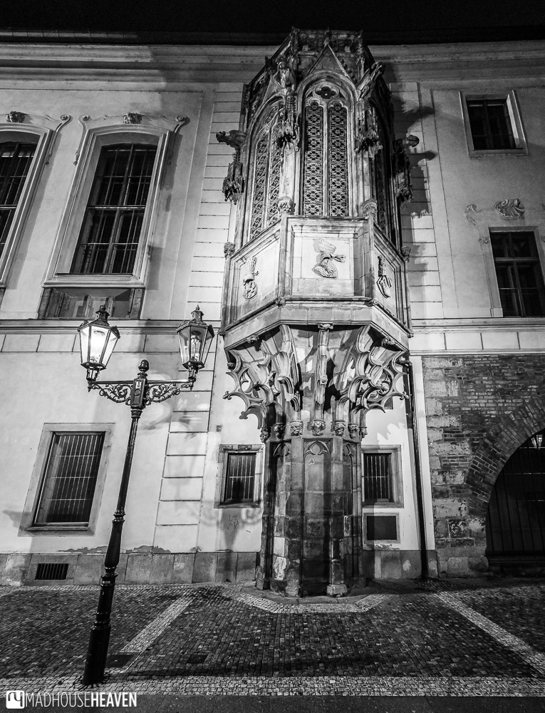 An imposing gothic balcony with many curlicues and embellishments, looking spooking in the night