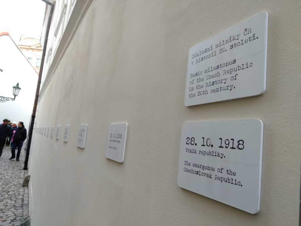 White cards on a small alley in Prague showcasing the timeline of Czech history in the 20th Century
