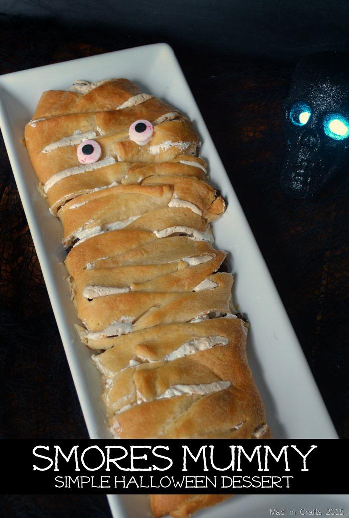 crescent roll mummy dessert on a white platter next to a skull