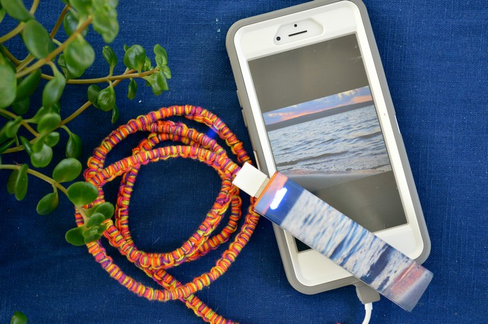 A close up of a cell phone and a colorful charger cable