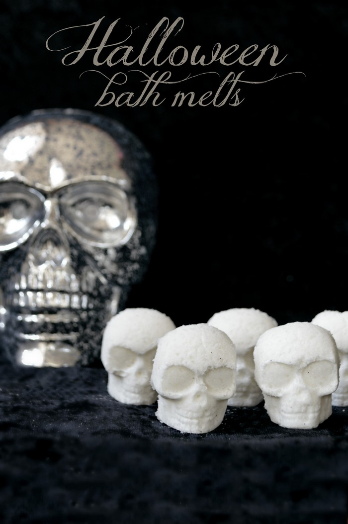 white skull shaped bath bombs and silver skull on a black background