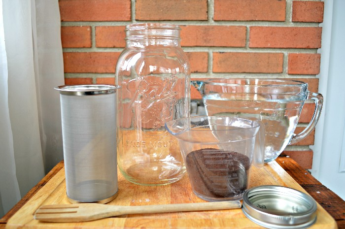 supplies needed to make cold brew in a mason jar: jar strainer, large mason jar, coffee, water, spoon