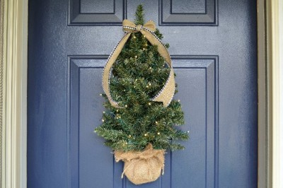 Mini Christmas tree hanging on a blue front door