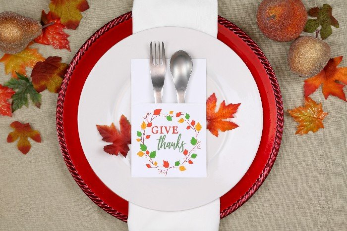 Printable utensil holder that reads Give Thanks, silverware, white plate with red charger