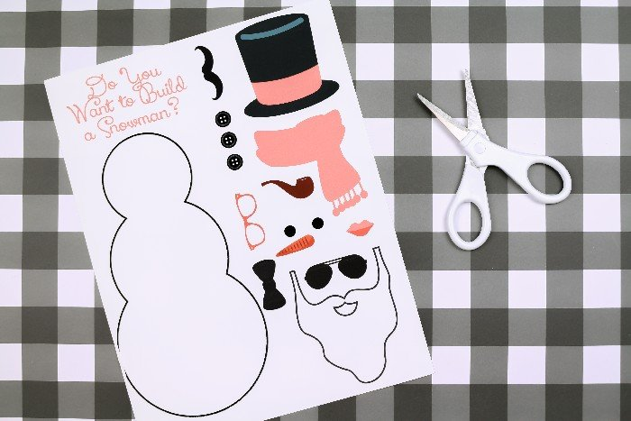 printable snowman paper doll PDF and scissors on a plaid background