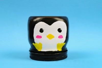 Penguin painted mason jar on a blue background