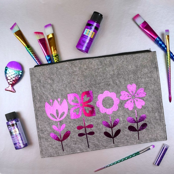 foil vinyl flowers on a zipper pouch with purple craft supplies on a silver background