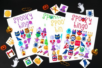 pile of printable halloween bingo cards on a black background