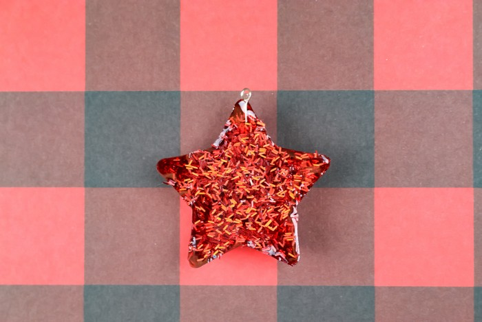 glitter resin star ornament on a plaid background