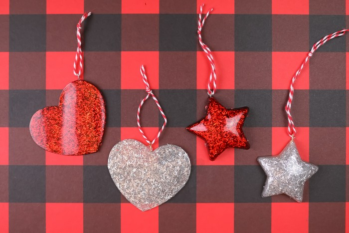 glitter resin heart and star ornaments on a plaid background