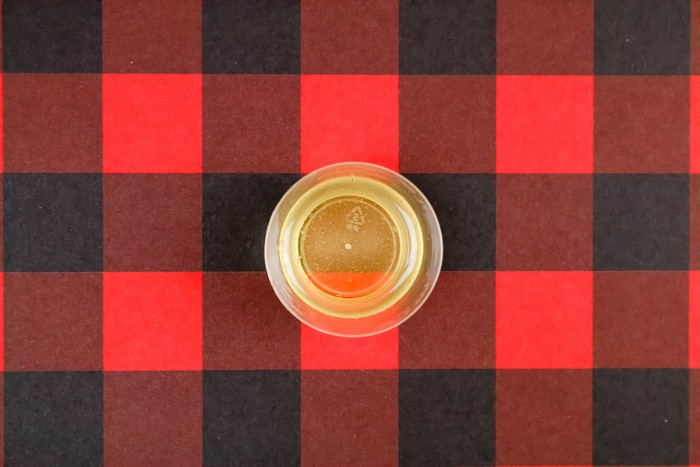 mixed resin in a small cup on a plaid background
