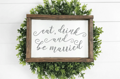farmhouse style Eat, Drink and Be Married sign on a green wreath