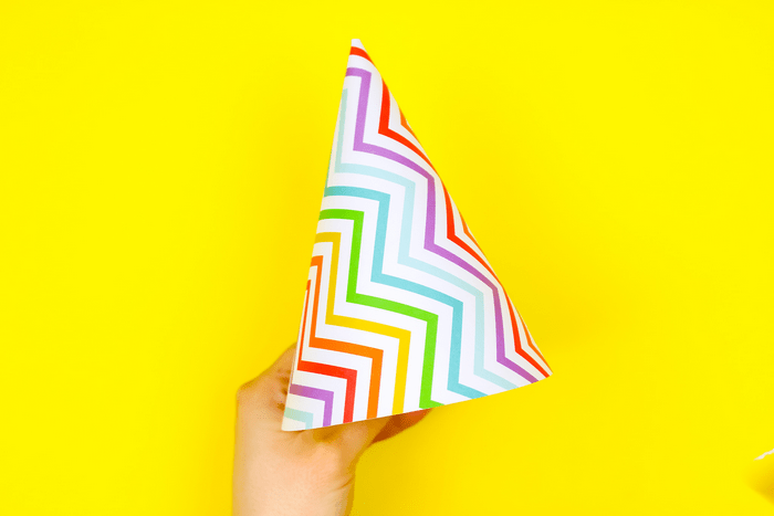 Hand holding a colorful paper party hat in front of a yellow background