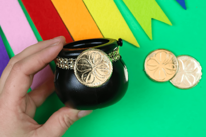 hand holding a mini pot of gold on a green background with rainbow bunting