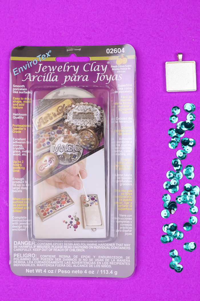 package of EnviroTex Jewelry Clay, pendant bezel, and teal sequins on a purple background