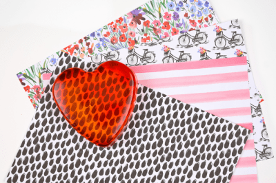 red resin heart paperweight on patterned scrapbook paper
