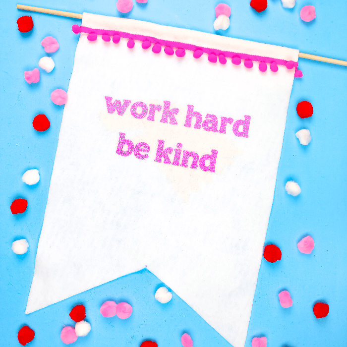 white felt banner that says work hard be kind on a blue background with pom poms