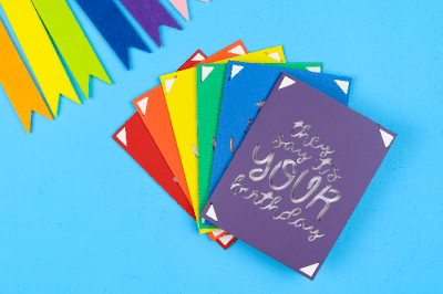 rainbow of Cricut insert cards for birthdays on a blue background