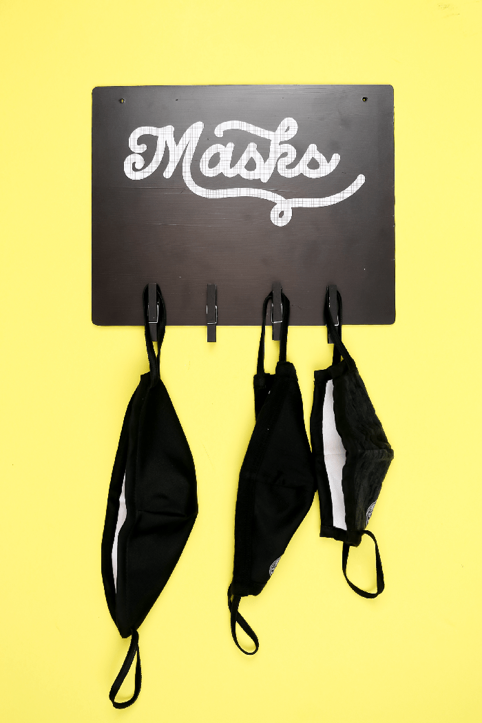 black vinyl mask sign on a yellow background