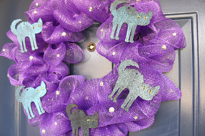purple mesh wreath with black cat shapes and rhinestones on a blue door
