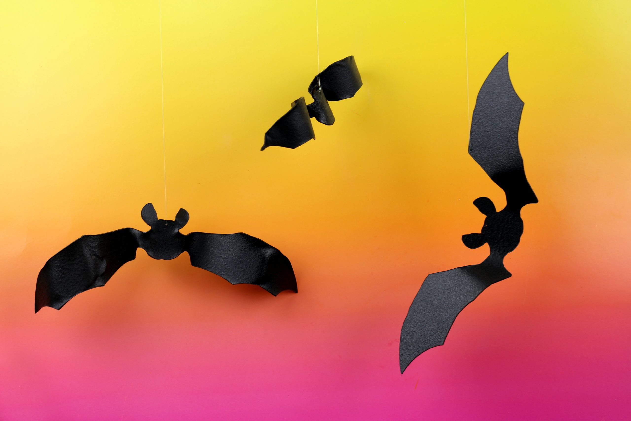 black bat shapes cut out of worbla plastic on pink and orange background