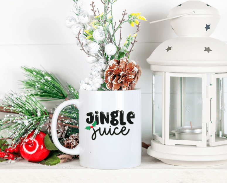 Jingle Juice SVG design on a white mug next to a lantern and greenery
