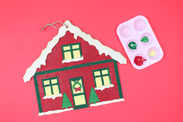 Painted Christmas house sign with paint palette on a red background