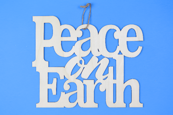 unpainted wood Peace on Earth sign on a blue background