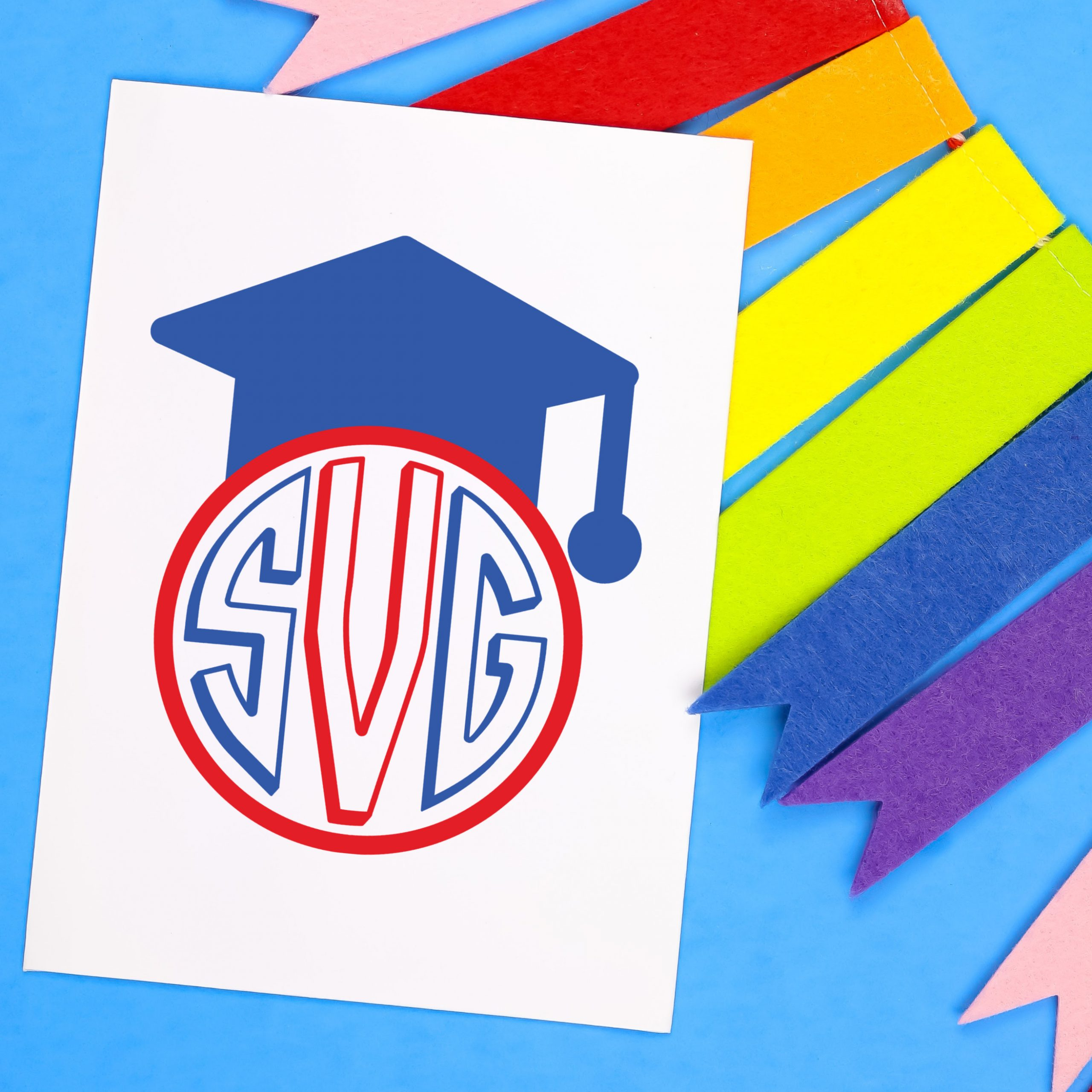 Colorful bunting and white card with a blue and red graduation monogram