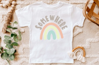 White-t-shirt-with-pastel-Somewhere-Over-the-Rainbow-SVG-on-a-tan-rug