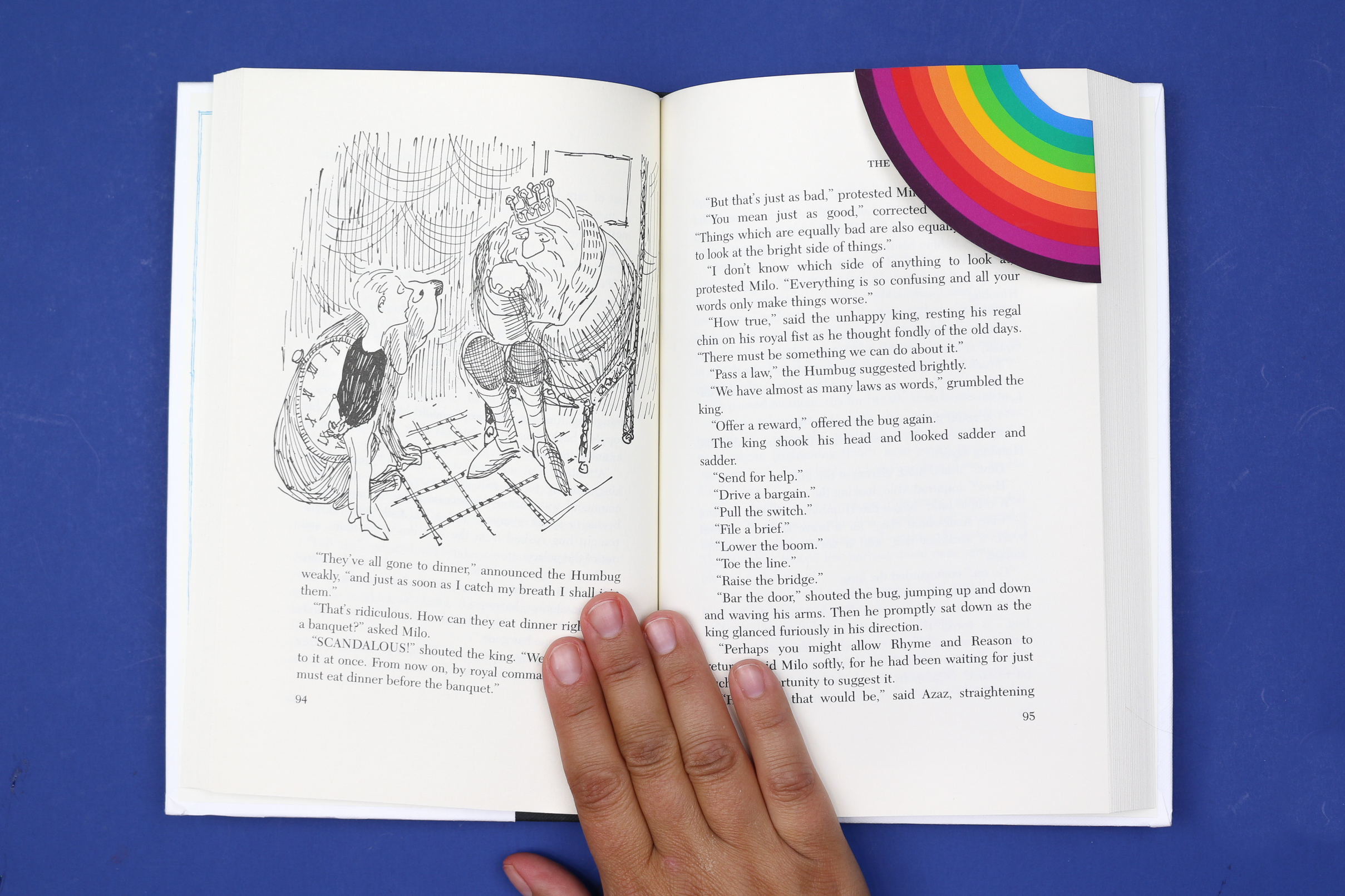 hand holding a book with a rainbow corner bookmark