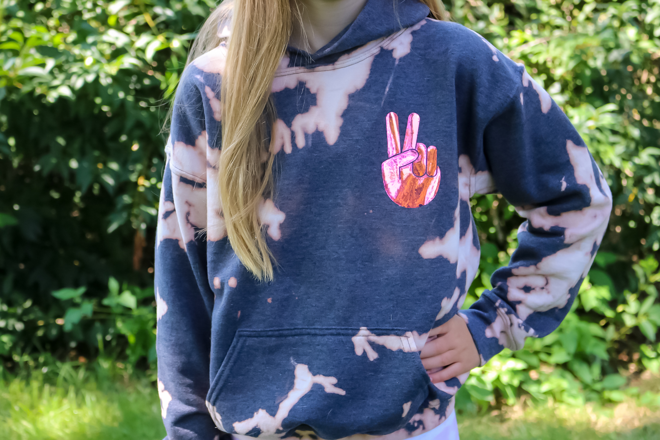 girl wearing bleach dyed sweatshirt with holo vinyl decoration